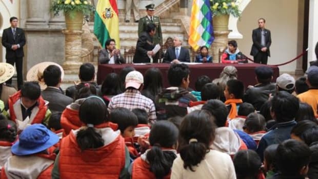 Eddy Roman Davalos Cayo, 15 Vice President of the Union of Child and Adolescent Workers, and children sit with Bolivian vice president Alvaro Garcia Linera and other leaders at the signing of the new Boys, Girls and Adolecents' code on July 17, 2014.
