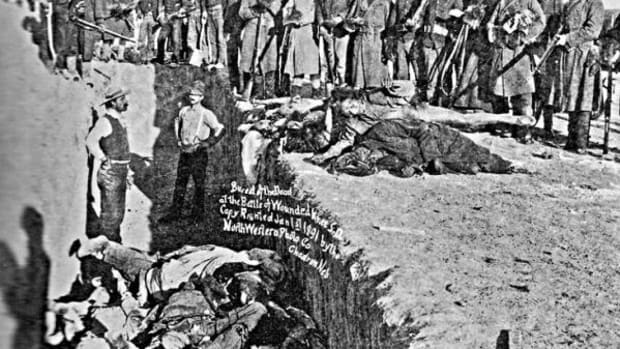 Victims of the Wounded Knee Massacre of December 29, 1890 are loaded into a mass grave, surrounded by their killers and volunteers who were paid $2 for every body buried.