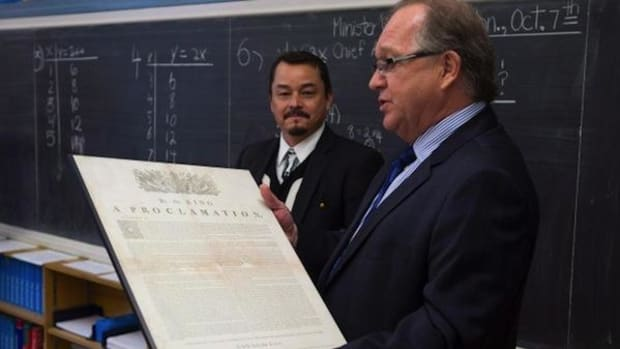 Aboriginal Affairs Minister Bernard Valcourt, right, and Assembly of First Nations National Chief Shawn A-in-chut Atleo visit a seventh-grade classroom in October 2013 just before the federal government released a draft of education reform legislation. Valcourt is holding a copy of the Royal Proclamation, which celebrated its 250th anniversary this year.