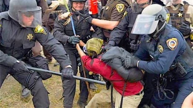 A woman water protector carrying a blue prayer stick is arrested by heavily armed police.