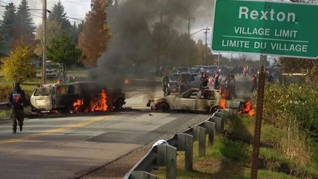 Police cars burn at a Mi'kmaq protest against shale-gas exploration in New Brunswick, Canada
