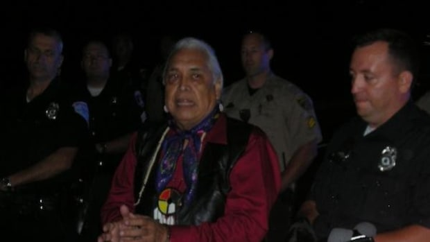 Nez Perce Tribal Chairman Silas Whitman, in handcuffs, appeals for tribal members and other protesters to remain calm after he and other tribal elected leaders were arrested during a blockade of equipment bound for the tar sands Monday August 5.