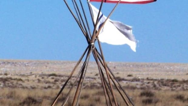 A 33-star American flag, white flag, and lodge poles at Sand Creek Massacre National Historic Site.
