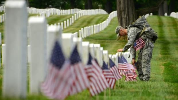 Sgt. Titus Fields, infantryman, Honor Guard Company, 3d U.S. Infantry Regiment (The Old Guard), places an American flag in front of a gravestone in Arlington National Cemetery.