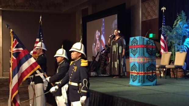 Niniau Simmons, Department of Hawaiin Home Lands, gives the blessing and welcome prayer Monday morning at the 2016 AMERIND Risk | NAIHC Annual Convention & Tradeshow general session. Pictured in front: Royal Guard of the Hawaii Air National Guard.