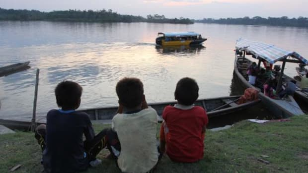 Kukama boys watch a boat leave the community of Dos de Mayo in Peru's Loreto region after a meeting between community leaders and government officials about the toxic condition of the villages drinking water.