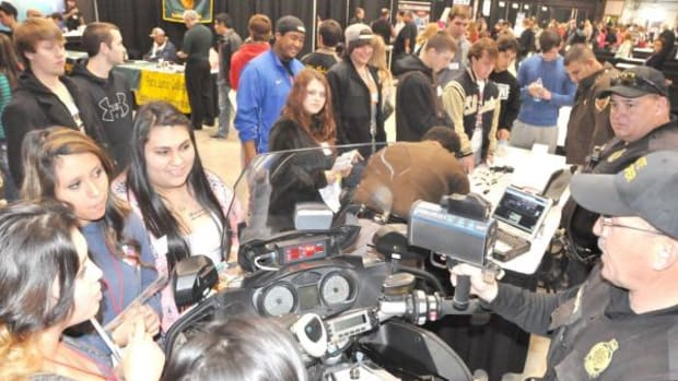 Trooper Ron Watson of the Oklahoma Highway Patrol demonstrates how to use a radar gun for a group of McAlester High School students during the 2015 Choctaw Nation Career Expo on Feb. 25, 2015.