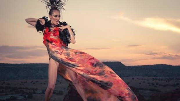 "Dress designed by Orlando Dugi, Navajo. Cape and dress from ""Desert Heat"" Collection, 2012. Paint, silk, organza, feathers, beads, and 24k gold; feathers. Hair and makeup: Dina DeVore. Model: Mona Bear."