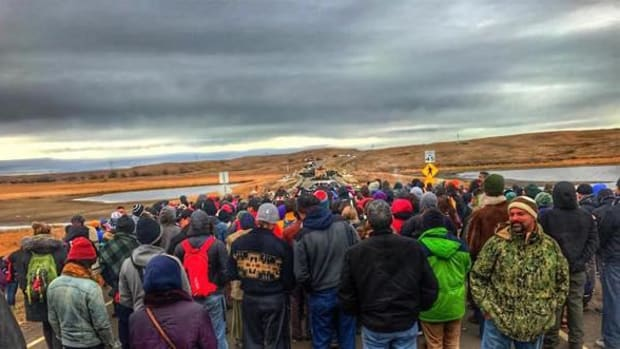 Hundreds of water protectors gathered along Highway 1806 for prayer as Chief Arvol Looking Horse carried the Pipe to negotiate peace with law enforcement.