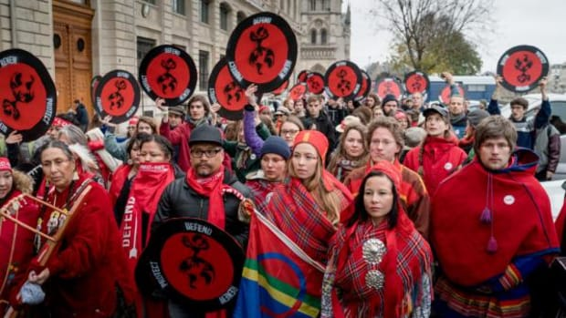 """Indigenous peoples march from Cathédrale Notre Dame de Paris on December 12, 2015, to the Pont des Arts or """"Love Bridge"""" to raise awareness of climate change."""