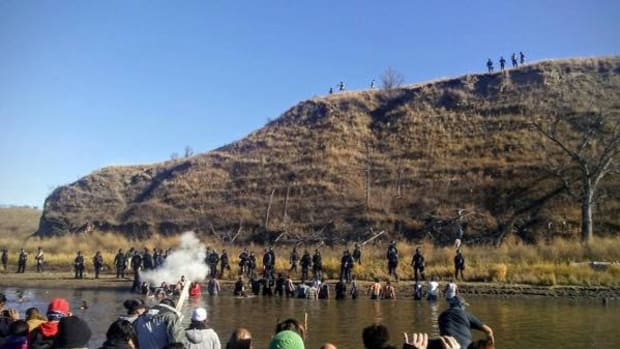 Water protectors try to cross a creek to stop the desecration of gravesites on a hill on federal land by the builders of the Dakota Access Pipeline. They were met with mace and pepper spray by North Dakota authorities stationed along the shore.
