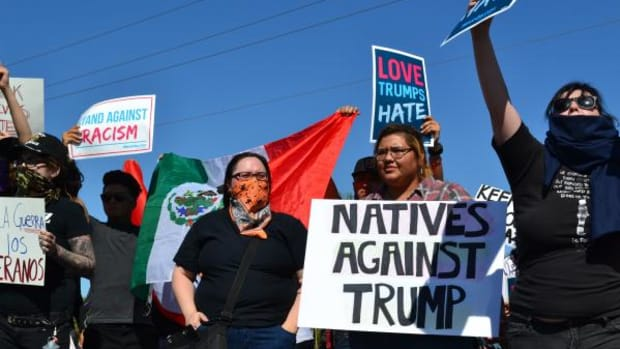 "Summer, who asked that her last name not be printed, of the Navajo Nation holds a sign reading, ""Natives Against Trump,"" during a protest on March 19, 2016 in Fountain Hills, Arizona."