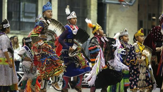 """Young female dancers come into the pow wow circle during the 42nd Annual """"Echoing Traditional Ways"""" Utah State University Pow Wow, in Logan, Utah."""