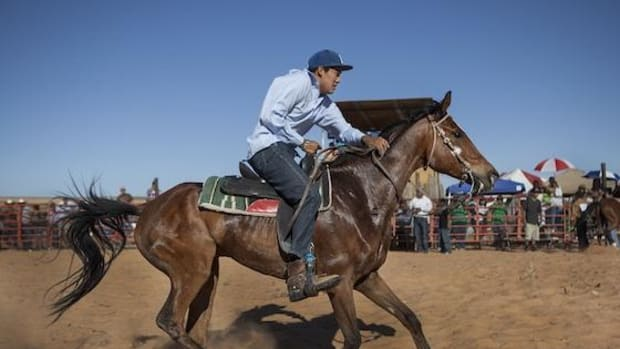 Bennett Padilla, 23, of Ojo Encino, N.M. races past the crowd during the second exchange of the relay race on Saturday morning, June 8, 2013. Bennett and his Starlake Racing team took third place in the Red Mesa, Navajo Nation horse race, part of a youth appreciation weekend.