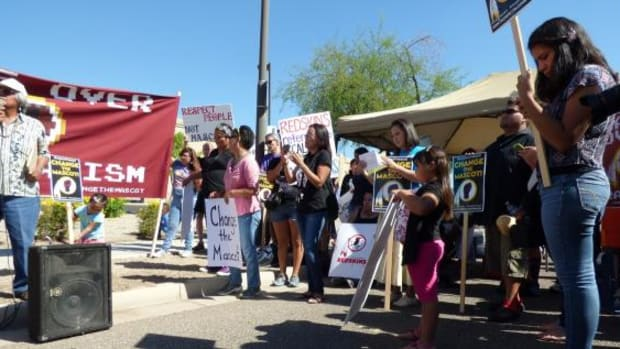People supporting a name change listen as Virgil Ortiz of Laguna Pueblo speaks at the Anti-Redskins protest rally on October 11, 2014. Ortiz is an Professor at Arizona State University.
