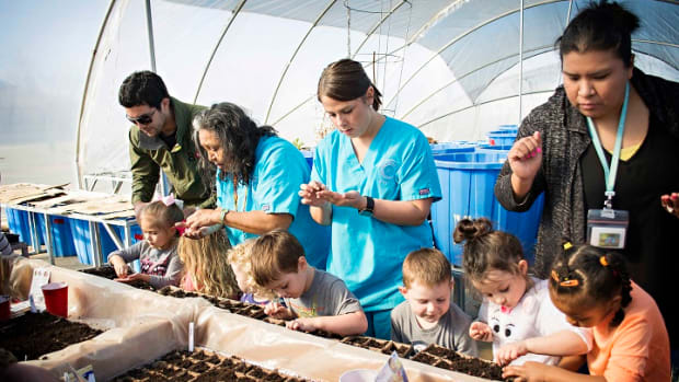 Chahta Foundation Executive Director Seth Fairchild, back left, and Choctaw Nation Head Start staff assist children participating in the Edible Schoolyard Project at the Choctaw Nation Hoop House.
