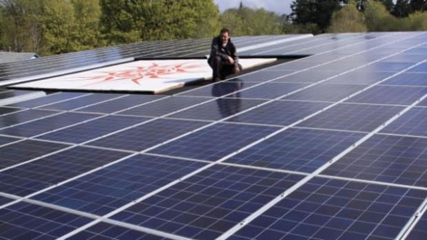 A member of the T'Sou-ke First Nation inspects solar panels.
