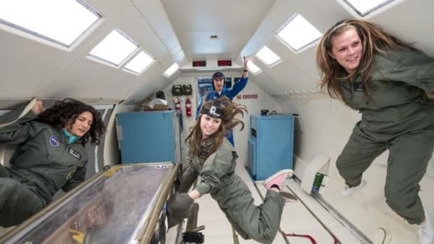 Molly Musselwhite works with the team's experiments in the glove box while Georgianna Revels, right, floats on the wall. NASA crew members look on.