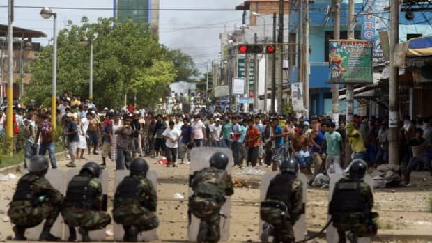 Police officers and miners clash during a protest in Puerto Maldonado, Peru, Wednesday, March 14, 2012. Thousands of illegal gold miners battled police for control of a regional capital in the Amazon basin on Wednesday and at least three people were killed by gunfire. The miners are fighting government efforts to regulate small-scale gold extraction, which is ravaging the rain forest, contaminating it with tons of mercury.