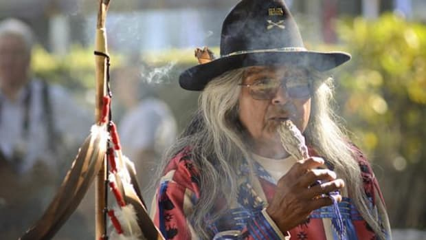 Delbert Davis, a member of Tule River Veterans Color Guard and Native Americans Veterans Post 1987 smudges himself with sage before the opening prayer at Native American Day ceremonies.