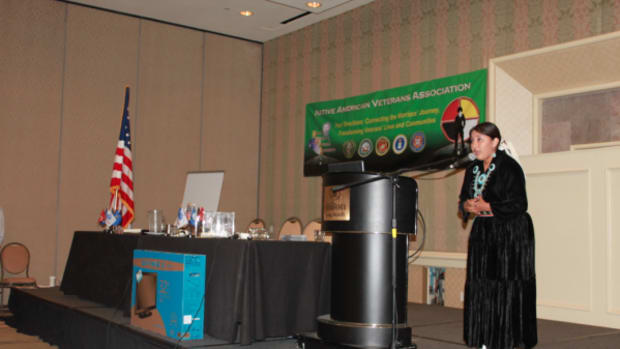 Singer and dancer DeCymbr' Maye Frank, Diné, sings the National Anthem in Navajo during the first annual Native American Veterans Association summit in Long Beach, California.
