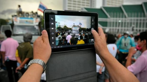 This image from November 24, 2012 shows a protester uses a tablet to photograph a rally on Makhawan Bridge in Bangkok, Thailand, organized by the nationalist Pitak Siam group. People everywhere, including journalists are using smartphones and tablets to report on events.