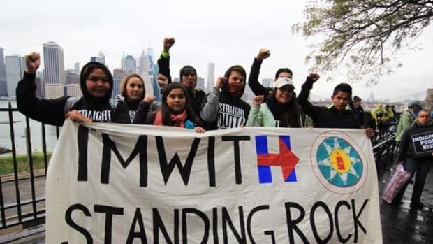 Standing Rock Youth gather with supporters on the Brooklyn Promenade with the Manhattan skyline as a backdrop.