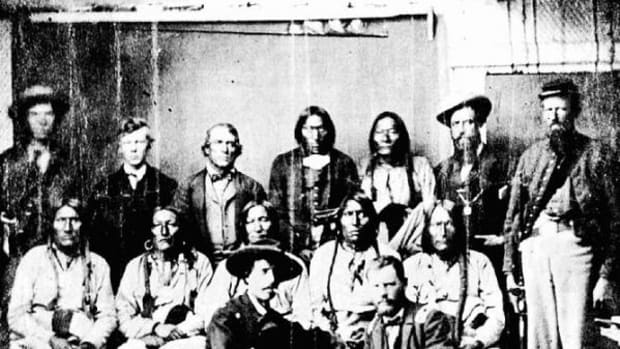 This rare photograph by an unknown photographer shows the ill-fated Cheyenne chief, Black Kettle, and a number of his associated at Camp Weld, on the outskirts of Denver. They had assembled there on September 28, 1864, for a peace council with Governor Evans and Colonel John M. Chivington, commander of the District of Colorado. Some of the identifications are uncertain. Pictured in the front row, kneeling, from left are: Major Edward W. Wynkoop, commander at Fort Lyon and later agent for the Cheyennes and Arapahoes; Captain Silas S. Soule, provost marshal, later murdered in Denver. Pictured in the middle row, seated, from left, are: White Antelope (or perhaps White Wolf), Bull Bear, Black Kettle, One Eye, Natame (Arapaho). Pictured in the back row, standing, from left are: Colorado militiaman, unknown civilian, John H. Smith (interpreter), Heap of Buffalo (Arapaho), Neva (Arapaho), unknown civilian, sentry. Another identification states that Neva is seated on the left and the Indian next to Smith is White Wolf (Cheyenne).