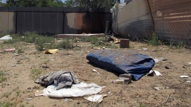 Bedding, clothing and broken glass litter a homeless encampment in Albuquerque, Monday, July 21, 2014, where three teenagers are accused of fatally beating two homeless Navajo men.