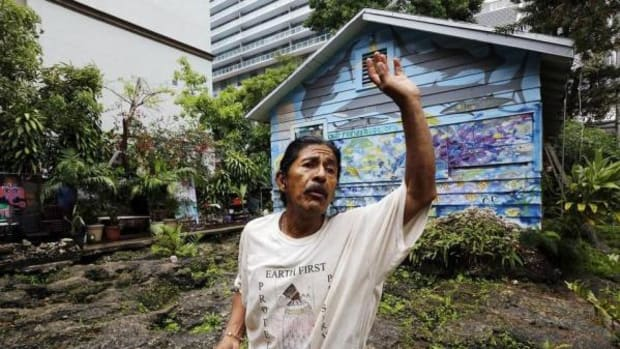 Ishmael Bermudez lives in his Miami home with his father and artist Burke Keogh. The home, at 87 SW 11th Street, is mostly surrounded by luxury high-rise buildings. Ishmael gestures as he explains how Native Americans used a conch shell to signal each other about the activities of the Europeans who settled in the area.