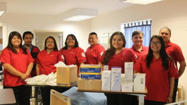 Registered nursing students of Navajo Technical University's School of Nursing take a photo next to supplies donated by Lovelace Medical Center. The supplies were donated after NTU's School of Nursing was hit hard by flash floods last September.