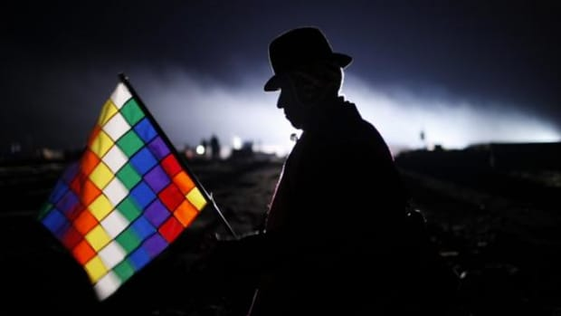 In this January 21, 2016, photo, an Aymara man holding a Wiphala flag is silhouetted against an early morning sky as he waits for the arrival of Bolivia's President Evo Morales to take part in an Andean ritual honoring the 10 years Morales has served as leader of the South American country, at the archaeological site Tiwanaku, Bolivia. Morales elevated the status of the multi-colored flag that represents the people of the Andes, making it the co-official flag of Bolivia.