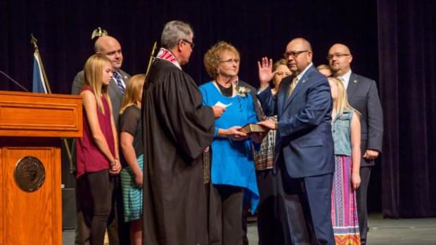 Chickasaw Nation Gov. Bill Anoatubby, right, takes the oath of office for an unprecedented eighth consecutive term during inauguration ceremonies Oct. 1 in Ada. Alongside Gov. Anoatubby are his wife, Janice, sons Brian, far left, and Chris, far right, and their families.  Tribal Supreme Court Chief Justice Mark Colbert, left, administers the oath of office.