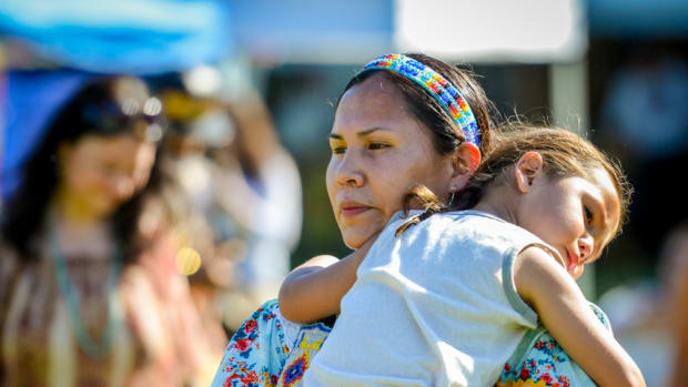 Tired from a long, fun weekend, Tayrn Walking Eagle-Mesteth carries her sleepy child at the Mother's Day pow wow in Canton, GA. Amy Morris