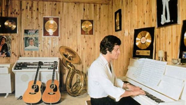The late Joe Dassin, an American-born French pop star, among his gold records in an undated photo