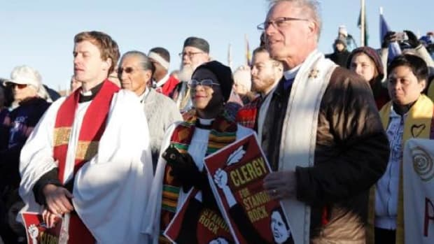 The Rev. Stephanie Spellers, canon to the presiding bishop for evangelism and reconciliation, center, and California Bishop Marc Andrus, right, join a circle of more than 500 interfaith allies standing in prayerful, peaceful solidarity with the Standing Rock Sioux Nation in their opposition to the route of the Dakota Access Pipeline.