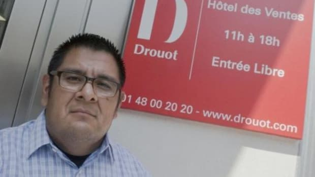 Sam Tenakhongva, poses for the media outside Drouot's auction house prior to the contested auction of Hopi Katsinam in Paris, France, Wednesday June 10, 2015. (AP Photo/Jacques Brinon)