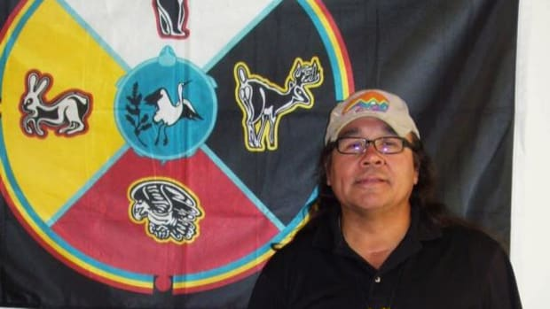 "Manidoogekek, standing in front of the Ojibwe tribal flag, which hangs on the wall of his office at Native American Lifelines in West Roxbury, Massachusetts. Some of the programs offered there include smoking cessation, one-on-one counseling, group counseling, HIV prevention, behavioral health and treatments for substance abuse. Manidoogekek proudly reports that ""plans for Red Road Recovery meetings and ceremony are in the works."" (By Donna Laurent Caruso)"