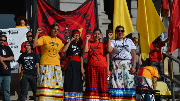 Organizers of the Four Directions March in Denver stand, fists up, on the west steps of the Colorado State Capitol on Saturday. Tessa McLean, second from right, said Christopher Columbus represents racism.