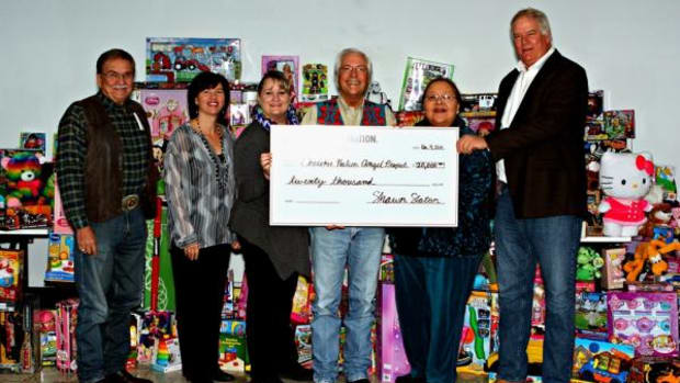 Officials from Cherokee Nation and Cherokee Nation Businesses present a $20,000 check to coordinators for the Cherokee Nation Angel Project. The annual campaign ensures Cherokee children in need receive clothing and other gifts at Christmas.