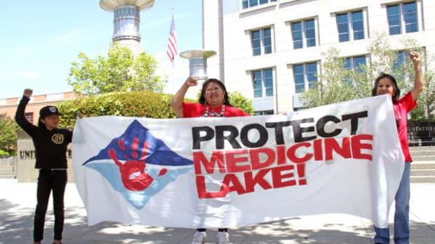 Pit River tribal members Laura Seal (center) and Jessica Jim (right) with the help of a young friend rally April 19 outside the Robert T. Matsui Courthouse in Sacramento, California where a federal judge ruled the Bureau of Land Management illegally extended geothermal leases in the sacred Medicine Lake Highlands.