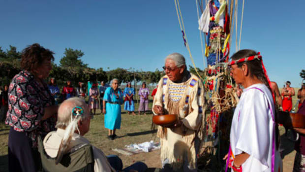 After the sundance, Chief Joe American Horse and Loretta Afraid of Bear honor ally Dayton Hyde with a naming ceremony. In the blue dress in the background is Beatrice Long Visitor Weasel Bear.