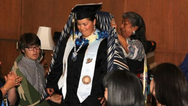 Victoria Garica, Chiricahua Apache/Round Valley, receives a Pendleton blanket from Native American Student Development staff during the May 18 UC-Berkeley Native graduation ceremony.