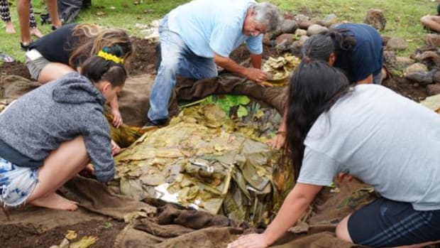 Native American Community Academy students from New Mexico learn to bake kalua in a traditional Hawaiian underground oven.