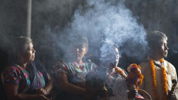 A woman wearing traditional indigenous dress carries incense as a procession enters the Basilica of Guadalupe in Mexico City on October 13, 2015. The Basilica celebrated its first ever Mass in the indigenous language of Nahuatl that day.