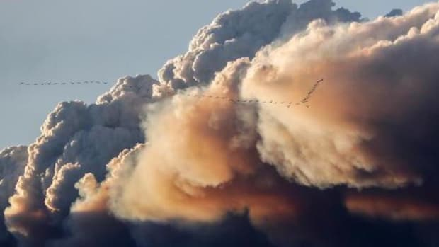 A flock of birds fly as smoke billows from the Fort McMurray wildfires in Kinosis, Alberta, May 5, 2016. The fires cover nearly 400 square miles and threaten at least one oil sands processing facility.