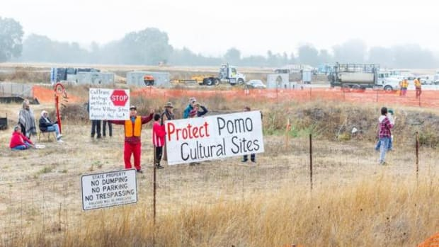 Protesters hold signs while workers continue work on the Willits Bypass, which will cut through Northern Pomo ancestral territory.