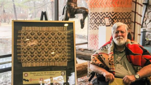 Tom Mooney sits next to his retirement gift from the staff of the Cherokee Heritage Center. The archivist retired December 6, which marked 38 years to the day that he started at the museum.