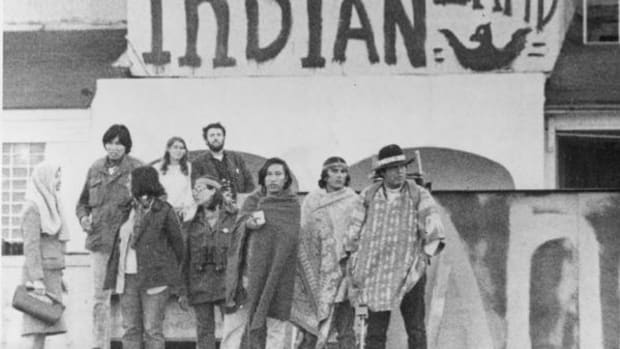 A group of Native American Indians, part of the Indians of All Tribes Inc., occupying the former prison at Alcatraz Island, stand under graffiti welcoming Indian occupiers to United Indian Property on the dock of Alcatraz Island, San Fransico Bay, Ca., Nov. 25, 1969. The occupiers are demanding a visit by Secretary of the Interior to discuss possession of the surplus mid-bay property.