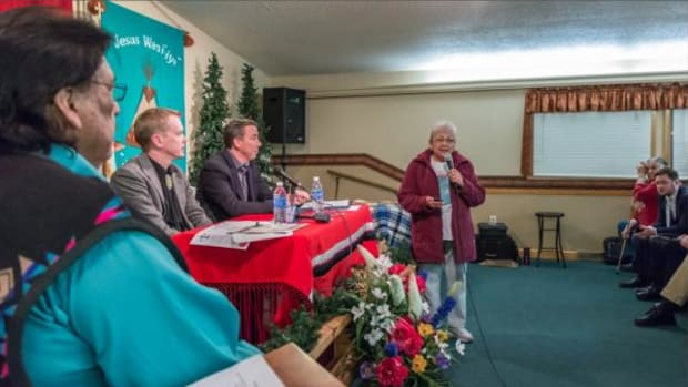 Sharon No Heart, center, addresses a crowd at the He Sapa New hope Church in Rapid City, South Dakota, on Monday. Residents had gathered to discuss recent racially motivated incidents in the city.